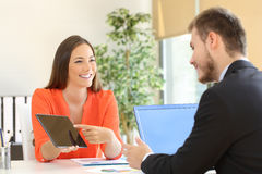Saleswoman trying to sell to a client. Saleswoman trying to sell products to a client showing them in a tablet at office stock images