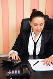 Saleswoman using calculator and looking on papers Stock Photo