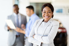 Saleswoman vehicle showroom. Beautiful young african saleswoman standing inside vehicle showroom stock photo