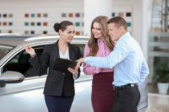 Saleswoman working with clients in car dealership. Young saleswoman working with clients in car dealership stock image