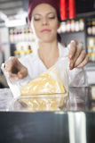 Saleswoman Wrapping Cheese In Grocery Store Royalty Free Stock Images