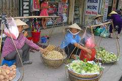 Saleswomen of fruits. These two young girls selling fruit on the street. In Vietnam, in neighborhoods, much of the food trade is in the street by street vendors Stock Image