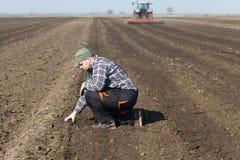 Saleté de jeune exploitant agricole tandis que le tracteur laboure le champ photos stock