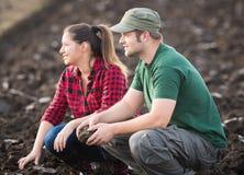 Salet? d'examen de jeunes exploitants agricoles tandis que le tracteur laboure le champ photos libres de droits