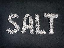 Salez le mot du sel brut de mer sur la pierre photographie stock