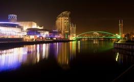 Salford kajer på natten, Lowry och milleniumbron, suddig reflexion på vattnet, Manchester UK Royaltyfri Fotografi