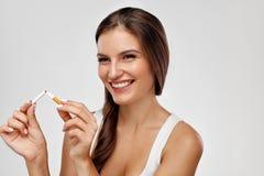Salga la imagen antifumador rendida Smoking Mujer feliz hermosa que sostiene el cigarrillo roto Fotografía de archivo