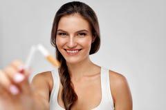 Salga la imagen antifumador rendida Smoking Mujer feliz hermosa que sostiene el cigarrillo roto Fotos de archivo