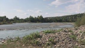 Salga a la orilla rocosa de un río de la montaña Una corriente rápida es visible, en el horizonte allí es una cadena de montaña almacen de metraje de vídeo