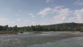 Salga a la orilla rocosa de un río de la montaña Una corriente rápida es visible, en el horizonte allí es una cadena de montaña almacen de video