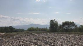 Salga a la orilla rocosa de un río de la montaña Una corriente rápida es visible, en el horizonte allí es una cadena de montaña metrajes