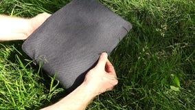 Salga un ordenador portátil blanco de la cubierta en la hierba verde almacen de video