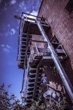 Salida de incendios oxidada del edificio de ladrillo rojo abandonado Foto de archivo libre de regalías
