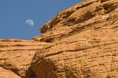 Salida de la luna sobre el barranco rojo de la roca Fotos de archivo