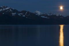 Salida de la luna sobre las montañas con la reflexión de la Luna Llena Foto de archivo