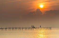 Salida del sol agradable de la familia en el puente de madera Imagen de archivo