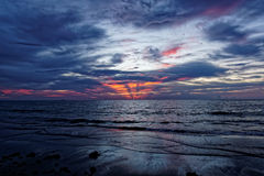 Salida del sol anaranjada ardiente sobre el océano Gray Clouds Imagen de archivo libre de regalías