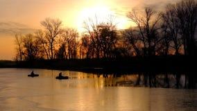 Salida del sol anaranjada, lago y pescadores en barcos