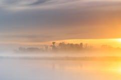Salida del sol anaranjada sobre un río salvaje brumoso foto de archivo