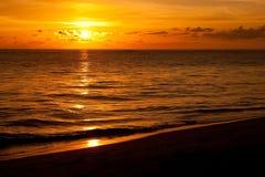 Salida del sol brillante en madrugada con la playa de la arena Foto de archivo libre de regalías