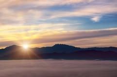 Salida del sol brillante, valle de la montaña y picos de montaña imagen de archivo libre de regalías