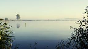 Salida del sol brumosa durante una mañana del verano del lago Foto de archivo libre de regalías