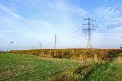 Salida del sol con el campo y el pilón eléctrico Fotos de archivo libres de regalías