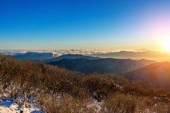 Salida del sol con la llamarada hermosa de la lente en las montañas de Deogyusan en wint imagenes de archivo