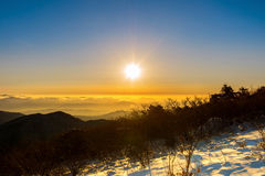 Salida del sol con la llamarada hermosa de la lente en las montañas de Deogyusan en wint fotos de archivo