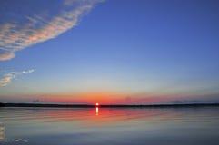 Salida del sol con la reflexión en agua tranquila Fotos de archivo libres de regalías
