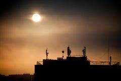 Salida del sol con las siluetas de la antena de la comunicación con un arsenal de platos fotografía de archivo