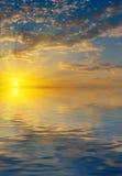 Salida del sol con los rayos del solsobre el mar Foto de archivo libre de regalías