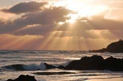 Salida del sol con sunrays sobre la playa rocosa Fotografía de archivo
