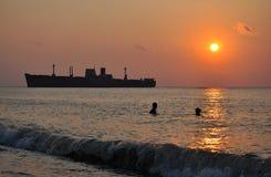 Salida del sol con una nave y los nadadores Fotografía de archivo libre de regalías