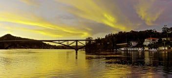Salida del sol costera coloreada de oro sobre el puente del rasgón Imagen de archivo libre de regalías