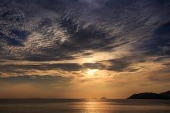 salida del sol de detrás las nubes de cúmulo de oro sobre el mar y la isla Imágenes de archivo libres de regalías