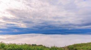 Salida del sol de la mañana, mar dramático de la nube, rocas gigantes y debajo del Br Foto de archivo