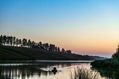 Salida del sol de la madrugada sobre el lago Silueta de un pescador que flota en un barco de pesca de goma inflable Imagen de archivo