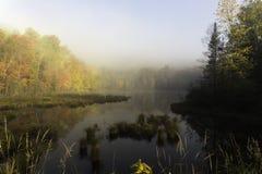 Salida del sol de la madrugada sobre un lago Fotos de archivo