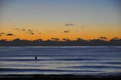 Salida del sol de la persona que practica surf sobre el océano Foto de archivo libre de regalías