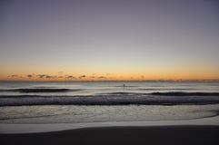Salida del sol de la persona que practica surf sobre el océano Foto de archivo