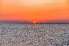 Salida del sol de la puesta del sol del rojo anaranjado en horizonte del océano del mar Imagen de archivo
