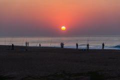 Salida del sol de la resaca de la playa de Roces de los pescadores Foto de archivo libre de regalías