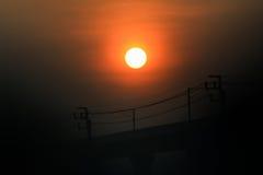 Salida del sol de la silueta sobre el carril del tren eléctrico Imagenes de archivo