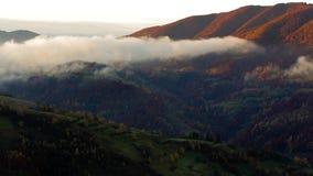 Salida del sol de niebla y caliente en montañas cárpatas metrajes