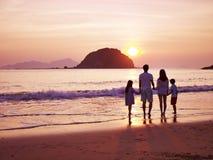 Salida del sol de observación de la familia asiática en la playa Imagen de archivo libre de regalías