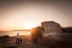 Salida del sol de observación del hombre y del perro detrás de la torre Genoese en Córcega Imagen de archivo libre de regalías