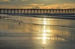 Salida del sol de oro en el embarcadero de la playa de la puesta del sol Fotografía de archivo libre de regalías