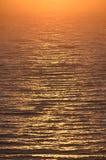 Salida del sol de oro en la trayectoria soleada del mar Foto de archivo