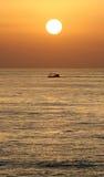 Salida del sol de oro en Marbella, España meridional con el océano y el barco Fotografía de archivo